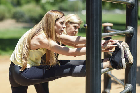 Mature woman exercising with her daughter in a park - JSMF01159