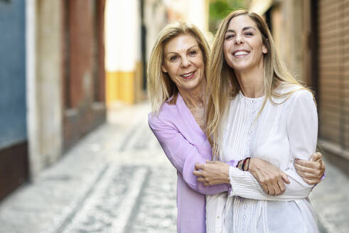 Happy mature woman with her daughter in the city - JSMF01171