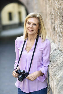 Mature woman with a SLR camera in the city - JSMF01183