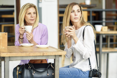 Mature woman with her daughter drinking coffee and tea sitting at an outdoor table in a cafe - JSMF01192