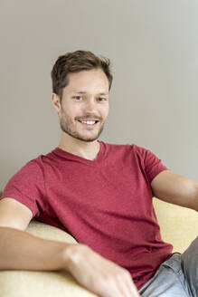 Portrait of a smiling man sitting on a couch - PESF01668