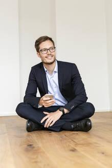 Deutschland, NRW, Köln, junger Mann in deuer Wohnung mit Smartphone, Businesskleidung - PESF01689