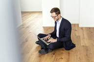 Smiling businessman sitting on the floor using laptop - PESF01695