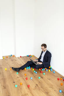 Businessman sitting on the floor using laptop surrounded by colourful balls - PESF01698
