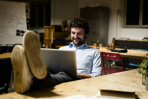 Businessman using laptop in office with feet on desk - GIOF06766
