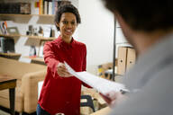 Businesswoman handing over paper to colleague in office - GIOF06775