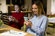 Two businesswomen using cell phones at desk in office - GIOF06787