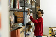 Portrait oif smiling businesswoman taking book from shelf in office - GIOF06799