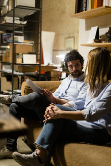 Businessman and businesswoman sitting on couch in office discussing papers - GIOF06811