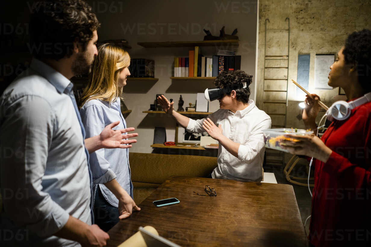 Colleagues looking at man wearing VR glasses in office - GIOF06841 - Giorgio Fochesato/Westend61