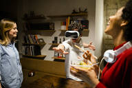 Happy woman with colleague wearing VR glasses in office - GIOF06844