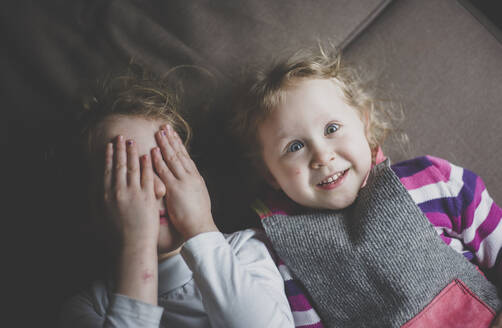 Portrait of two little sisters lying on couch having fun, top view - IHF00178
