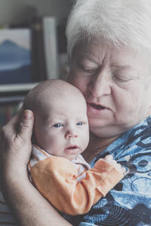 Portrait of grandmother with baby boy on her arms - IHF00189