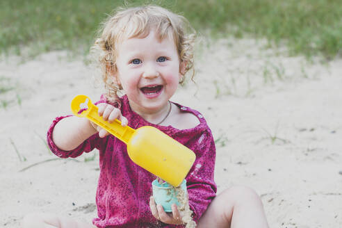 Portrait of happy toddler girl playing with sand - IHF00195
