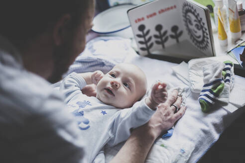 Father playing with his baby son on changing table - IHF00198