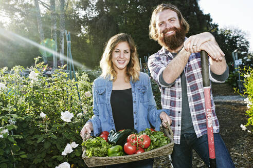 Couple standing with basket of vegetables in garden - BLEF10518
