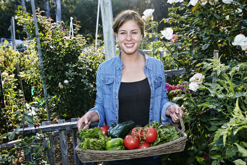 Mixed race woman holding basket of vegetables in garden - BLEF10521