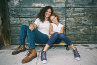 Mixed race mother and daughter sitting on skateboard - BLEF10587