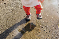 Caucasian baby girl walking in puddle - BLEF10611