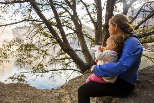 Caucasian mother and daughter sitting at lake - BLEF10614