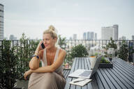 Caucasian woman talking on cell phone on balcony - BLEF10711