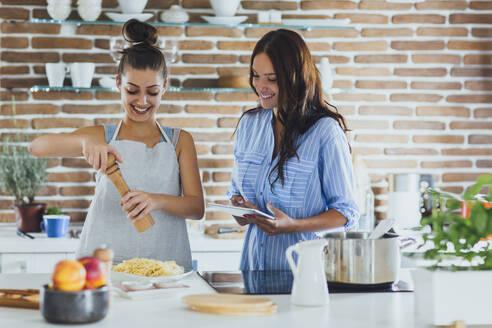 Caucasian women cooking pasta in kitchen - BLEF10756