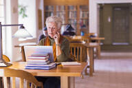 Older mixed race woman using laptop in library - BLEF10840