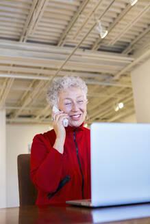 Older mixed race woman working in art gallery - BLEF10846