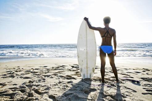 Black woman carrying surfboard on beach - BLEF10882