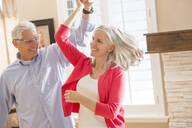 Caucasian couple dancing in living room - BLEF10942
