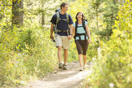 Caucasian couple hiking on path - BLEF10972