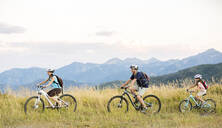 Caucasian family riding mountain bikes in field - BLEF10984