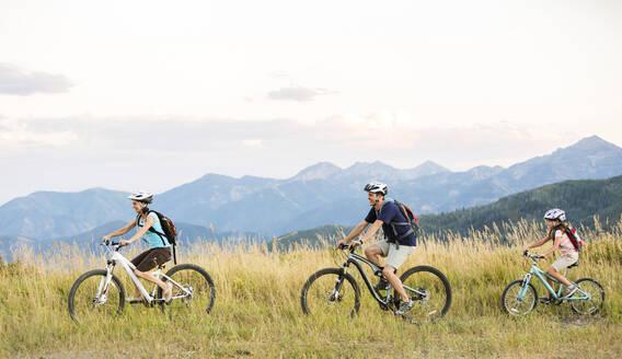Caucasian family riding mountain bikes in field - BLEF10984