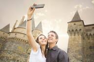 Caucasian couple taking selfie at castle - BLEF10990
