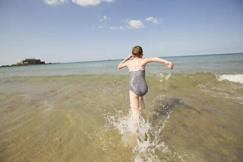 Caucasian girl splashing in waves on beach - BLEF10996