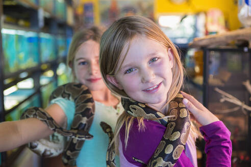 Caucasian girls playing with snakes in pet store - BLEF11023