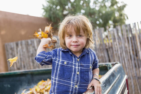 Caucasian boy playing in autumn leaves - BLEF11026