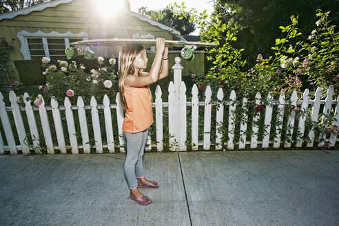 Caucasian girl carrying skateboard on sidewalk - BLEF11059
