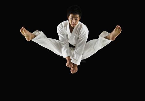 Asian male karate black belt kicking in air - BLEF11137