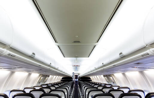 Empty chairs and compartments in airplane - BLEF11347