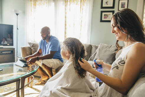 Mother styling hair for daughter in living room - BLEF11359