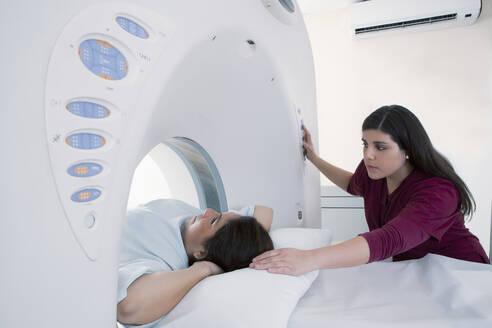 Hispanic nurse examining patient in MRI machine - BLEF11494