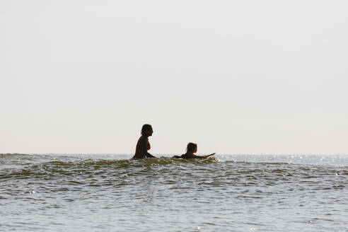 Mother and daughter surfing in waves - BLEF11527
