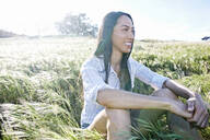 Mixed race woman sitting in field - BLEF11665