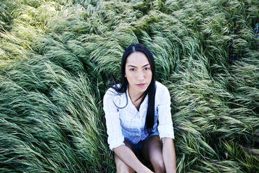 Mixed race woman sitting in grass - BLEF11668