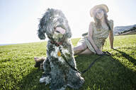 Caucasian woman sitting in field with dog - BLEF11698