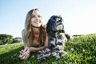 Caucasian woman sitting in field with dog - BLEF11701