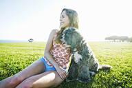 Caucasian woman sitting in field with dog - BLEF11704