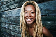 Black woman smiling at wooden wall - BLEF11710