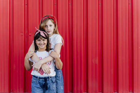 Sisters hugging in front of a red wall - ERRF01614
